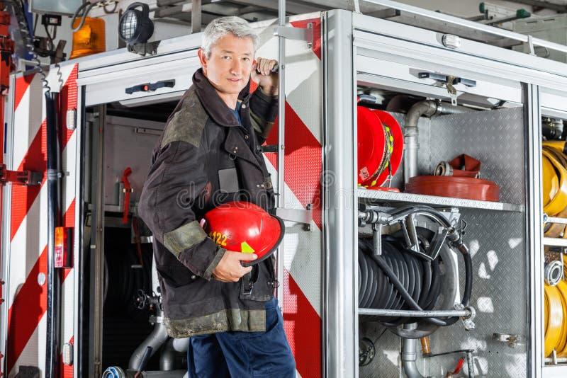 Vigile del fuoco sicuro che sta sull'autopompa antincendio fotografie stock