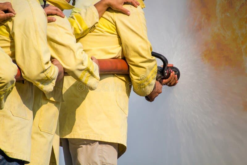 Vigili del fuoco che usando acqua dal tubo flessibile per l'estinzione di incendio all'addestramento di lotta del fuoco del grupp fotografia stock