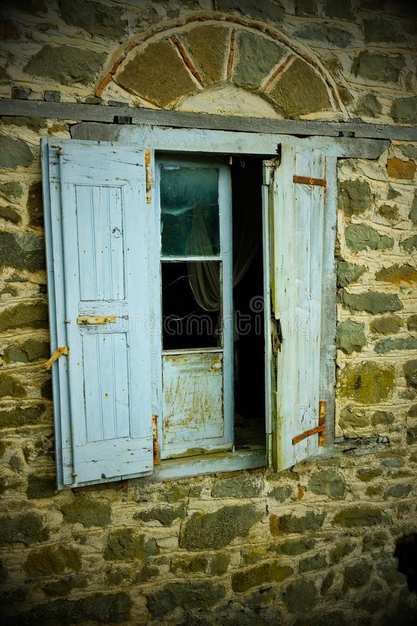 Vignette nostalgique, volets bleus fanés de fenêtre sur la Chambre abandonnée, Grèce image stock