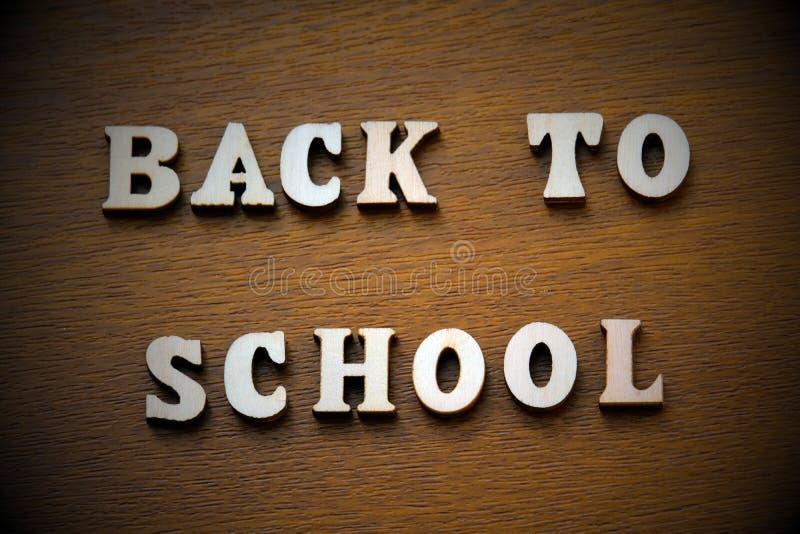 vignetting La inscripción de nuevo a escuela presentada de letras de madera en un fondo marrón imagen de archivo