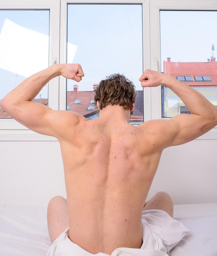 Vigorous exercise best but even light exercise better than no activity. Man muscular back stretching bed rear view. Get royalty free stock image