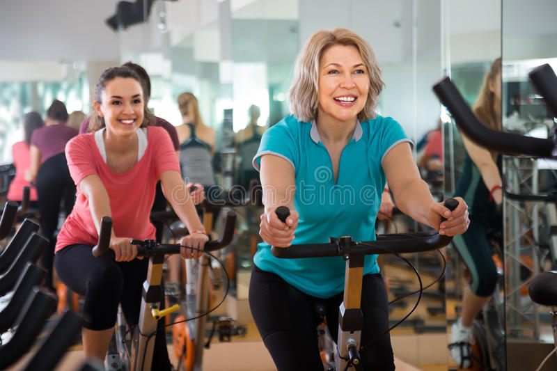 Vigorous females of different age training on exercise bikes royalty free stock photography