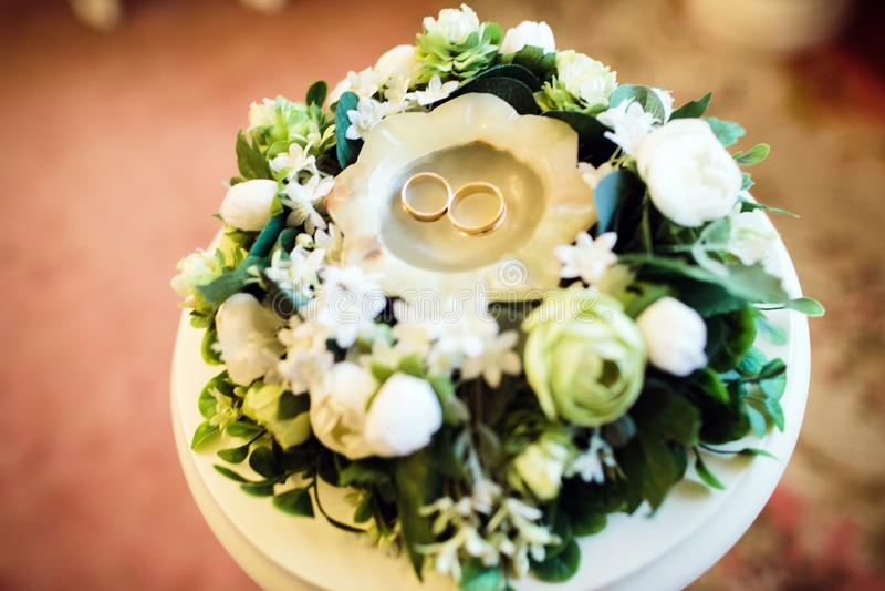 Vigselringar är i stearinljuset bland blommorna som gifta sig buketten arkivbild