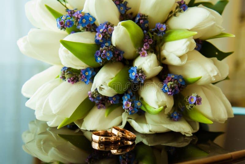Vigselringar av bruden och brudgummen på en härlig gifta sig bukett av vita tulpan arkivfoto