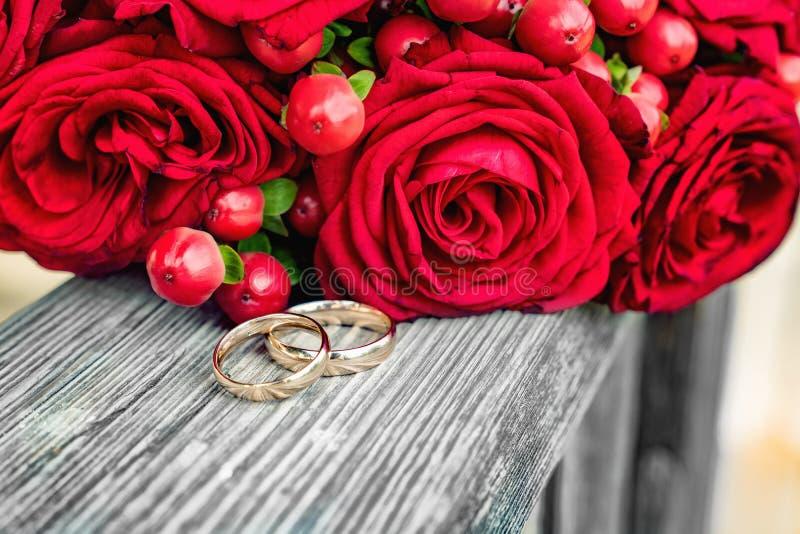 Vigselringar bredvid en röd rosbukett royaltyfria foton