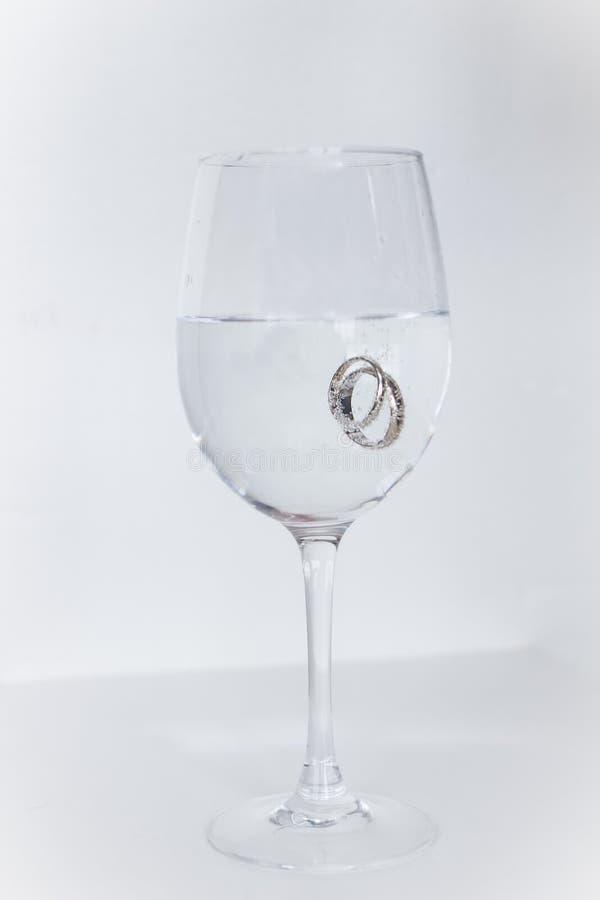 Vigselringar doppade i ett exponeringsglas som fylldes med champagne royaltyfri bild