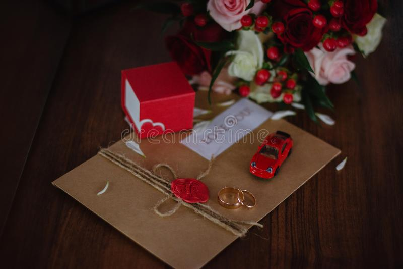 Vigselringar förälskelsebokstav, röd bil royaltyfria foton