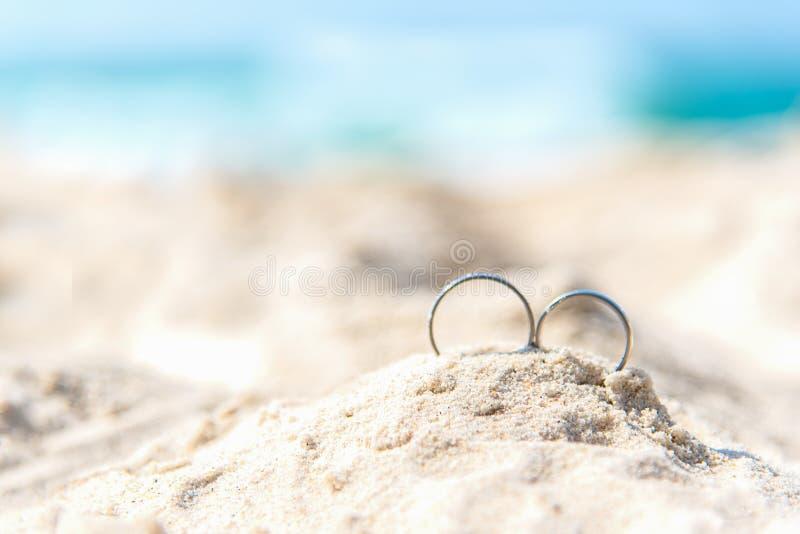 Vigselringar för parvän på den sandiga stranden Förlovningsringar i bröllopsresasemester i vändkretsar begreppshjärta över rose v arkivbilder