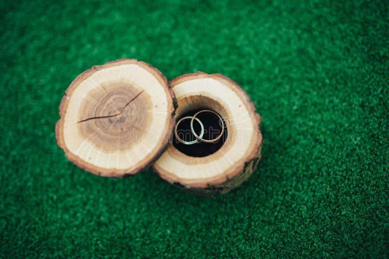 Vigselringar i en härlig och stilfull träask, på en grön bakgrund Begreppet av ett bröllop, ceremonin av trolovningen royaltyfri fotografi