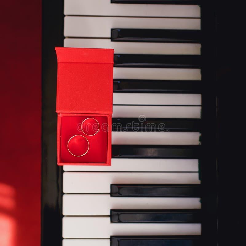 Vigselringar i röd ask på pianot royaltyfri fotografi