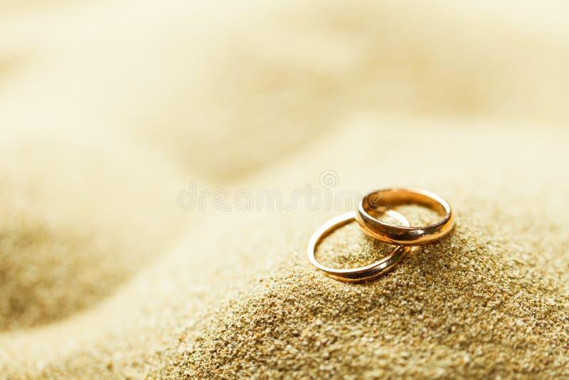 Vigselringar i sanden royaltyfri bild