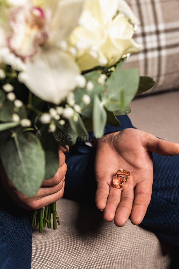 Vigselringar ligger och den härliga buketten som brud- tillbehör royaltyfri fotografi