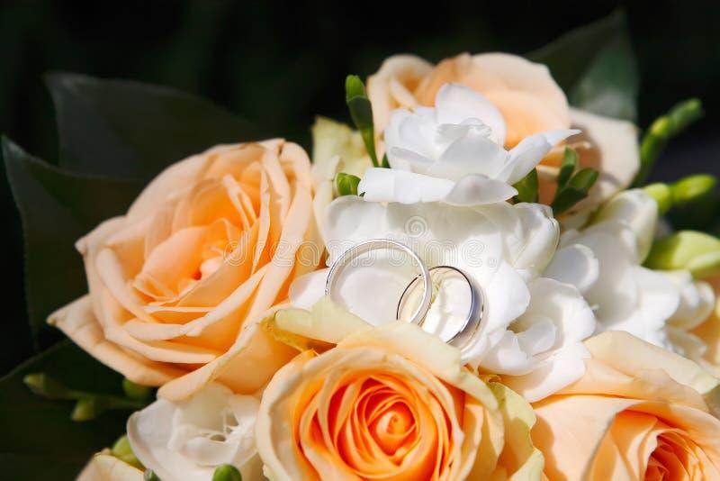 Vigselringar med blommor fotografering för bildbyråer