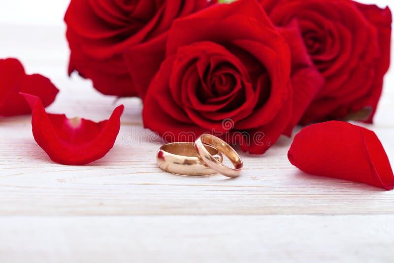 Vigselringar och bröllopbukett av kronblad för röda rosor arkivfoton