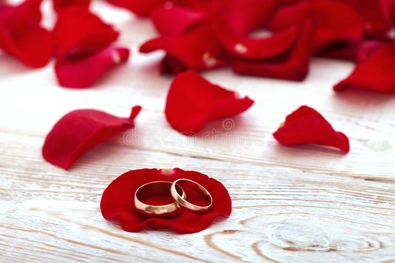 Vigselringar och bröllopbukett av röda rosor arkivbild