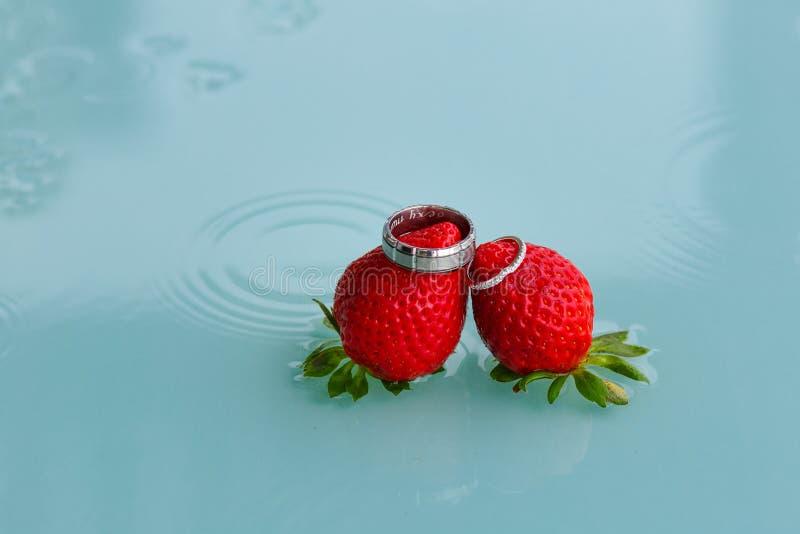 Vigselringar och jordgubbar royaltyfria bilder