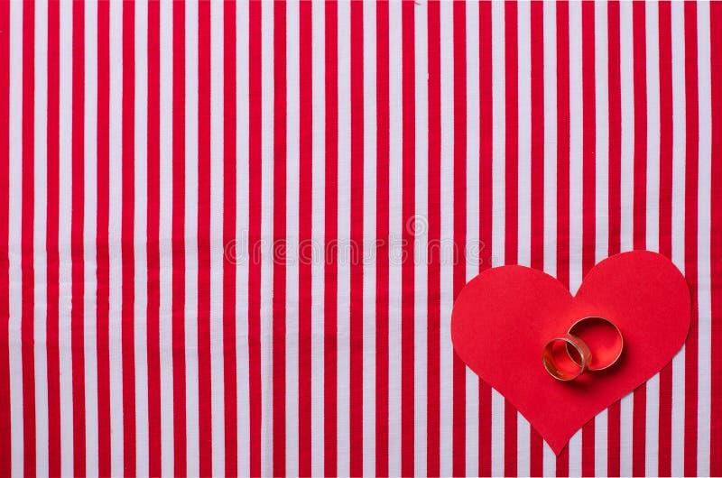 Vigselringar och pappers- hjärta royaltyfria foton