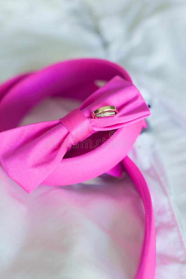 Vigselringar och rosa fluga arkivfoton