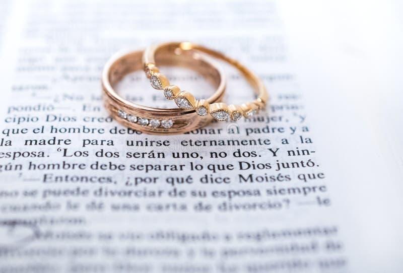 Vigselringar och spansk bibelscripture fotografering för bildbyråer