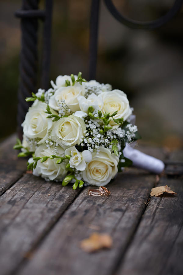 Vigselringar och vit Rose bukett