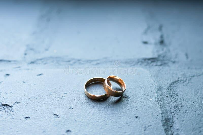 Vigselringar på blå tegelstenbakgrund för begreppsol för guld- cirklar förälskelse och bröllop fotografering för bildbyråer