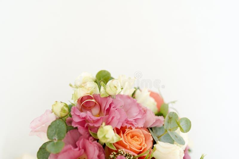 Vigselringar på buketten med blommarosor på en vit bakgrund med kopieringsutrymme Minsta begrepp Modell arkivbilder