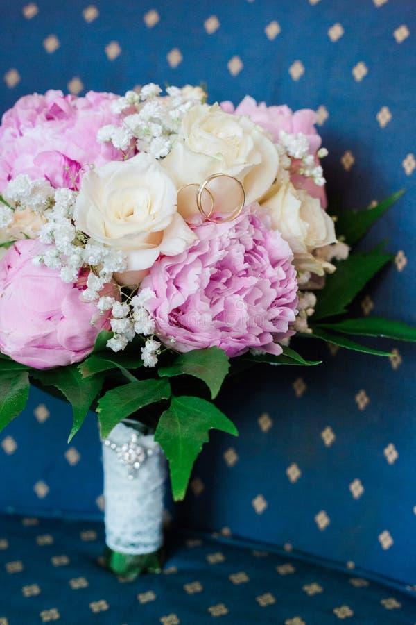 Vigselringar på en bukett av pioner och rosor på en blå bakgrund royaltyfri foto
