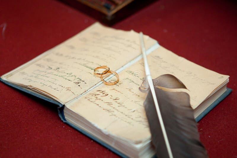 Vigselringar på en gammal bok arkivbild