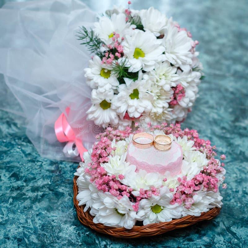 Vigselringar på en ställning av blommor och en brud- bukett av chamen royaltyfria foton