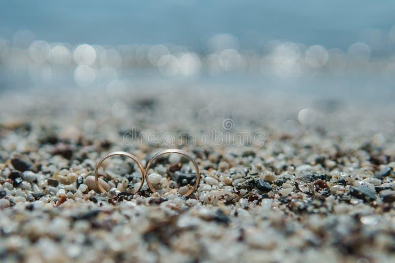 Vigselringar på kiselstensanden på stranden fotografering för bildbyråer