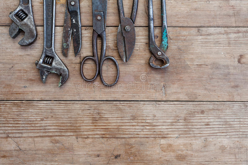 Viiew do vintage oxidou ferramentas na tabela de madeira velha: alicates, chave de tubulação, chave de fenda, martelo, tesouras d imagem de stock