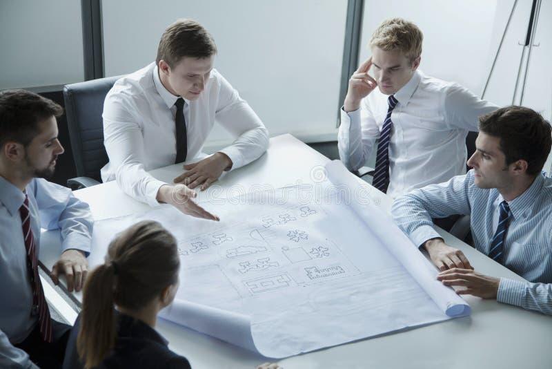 Vijf architecten die en over een blauwdruk in het bureau bespreken plannen stock fotografie