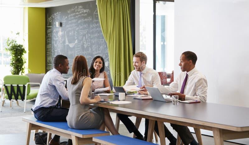 Vijf bedrijfscollega's in een informele vergadering op het werk royalty-vrije stock afbeeldingen