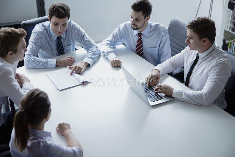Vijf bedrijfsmensen die een commerciële vergadering hebben bij de lijst in het bureau royalty-vrije stock fotografie