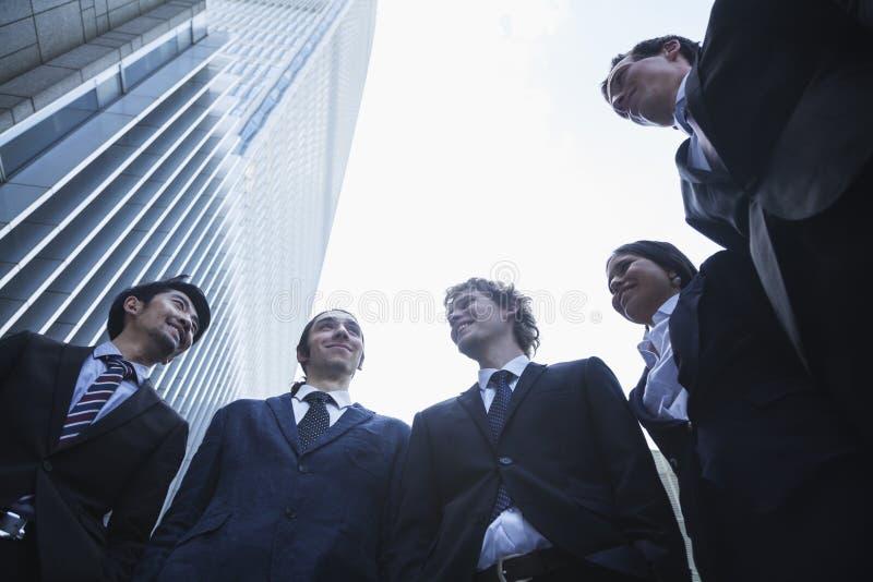Vijf bedrijfsmensen die in openlucht bevinden zich sprekend en glimlachend, Peking, Lage hoekmening stock afbeeldingen