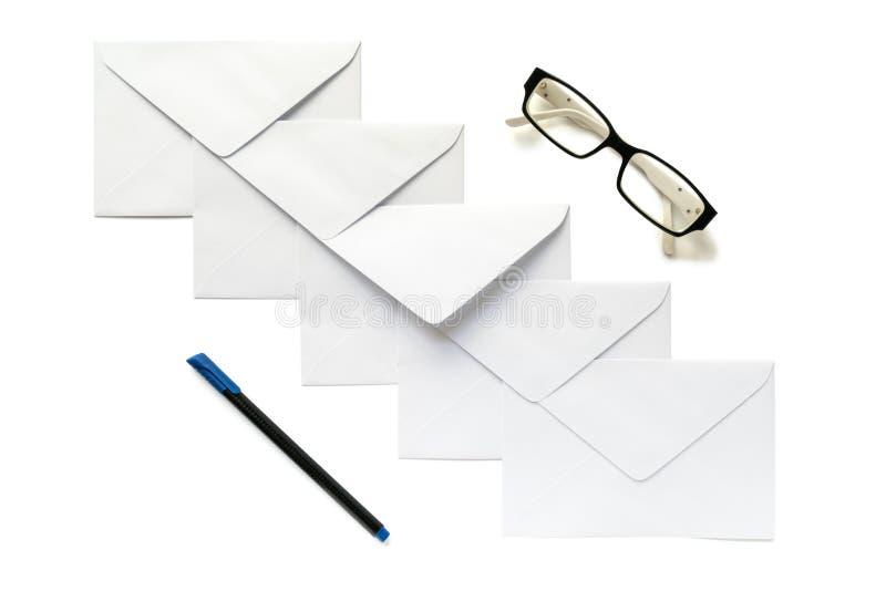 Vijf brievenenveloppen, oogglazen en een pen stock foto