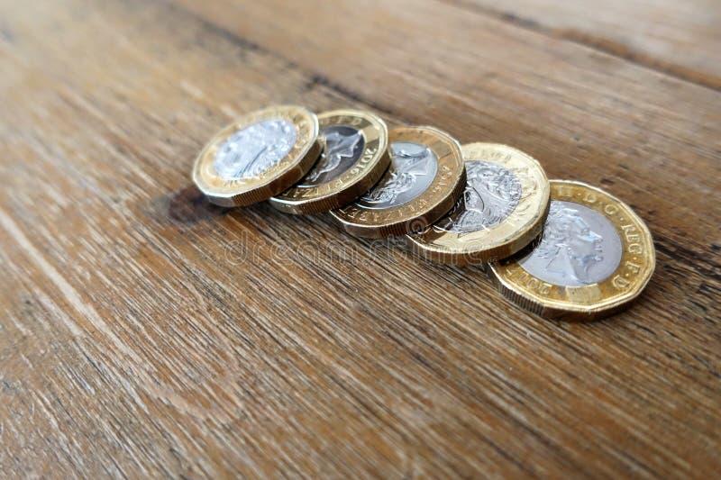 Vijf Britse Britse pondmuntstukken op een houten lijst stock afbeeldingen