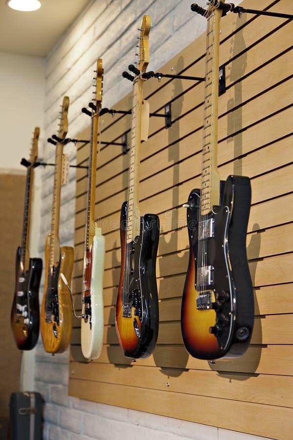 Vijf elektrische gitaren die op vertoningsrek hangen in opslag voor verkoop stock afbeeldingen