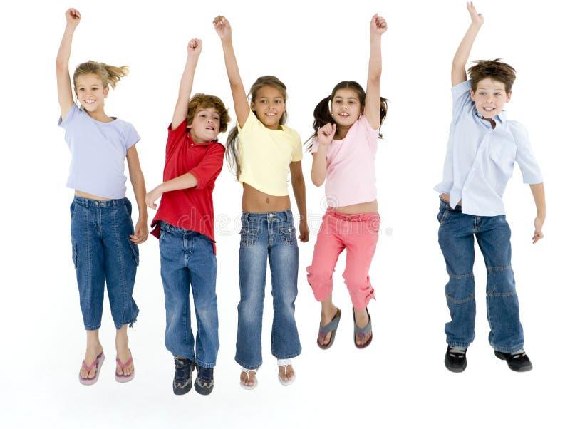 Vijf en vrienden die springen glimlachen stock afbeeldingen