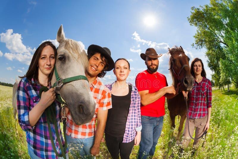Vijf gelukkige horseback ruiters in de zomerweide stock foto's