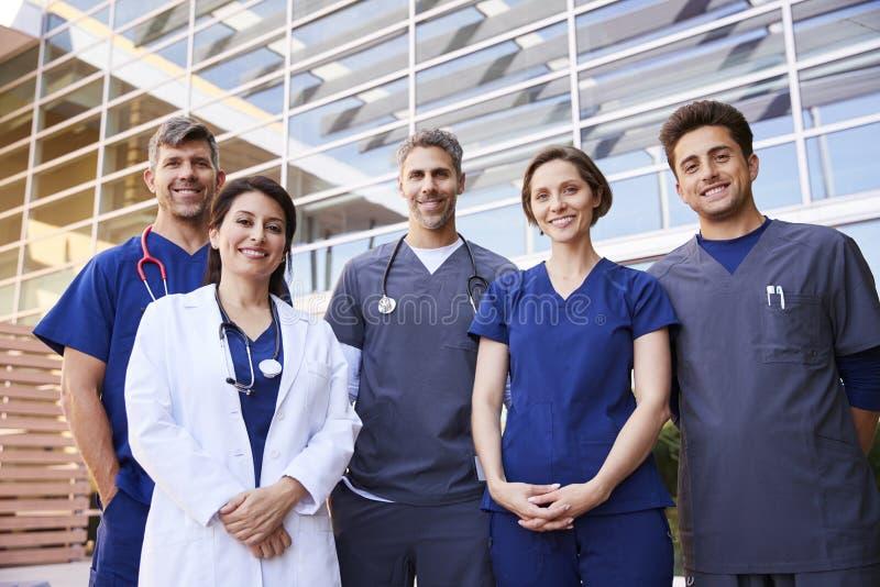 Vijf gezondheidszorgcollega's die, groepsportret zich in openlucht bevinden stock afbeelding