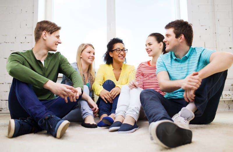 Vijf glimlachende tieners die pret hebben thuis stock afbeeldingen