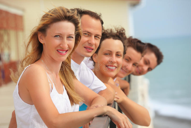 Vijf glimlachende vrienden op balkon stock afbeeldingen
