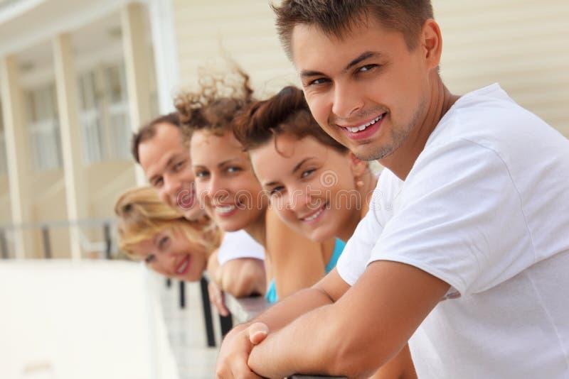 Vijf glimlachende vrienden op balkon stock foto's