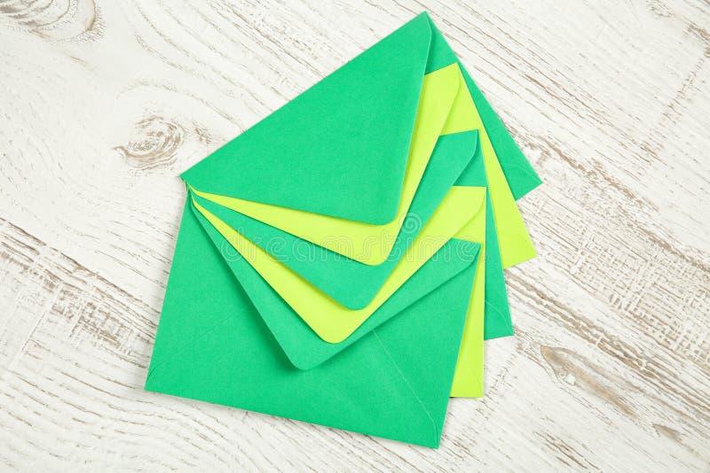 Vijf groene gekleurde die enveloppen van gerecycleerd document op een witte rustieke houten lijst worden gemaakt stock fotografie