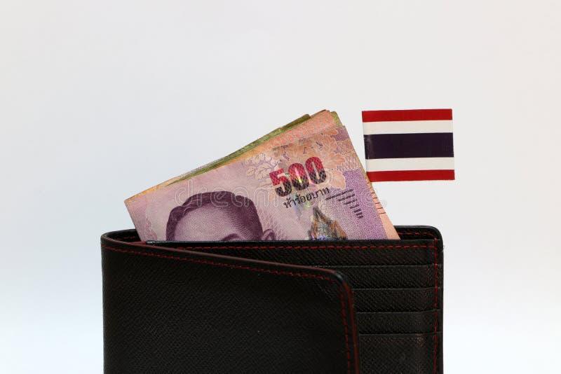 Vijf honderden bankbiljet Thais Baht en mini de natievlag van Thailand plakken op de zwarte portefeuille met witte achtergrond stock foto