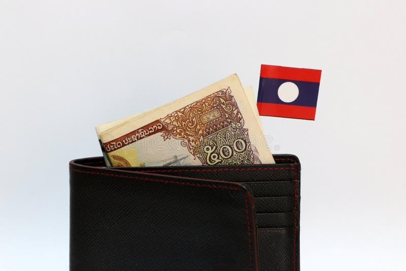 Vijf honderden bankbiljetmunt Lao Kip en mini de natievlag van Laos plakken op de zwarte portefeuille met witte achtergrond royalty-vrije stock fotografie