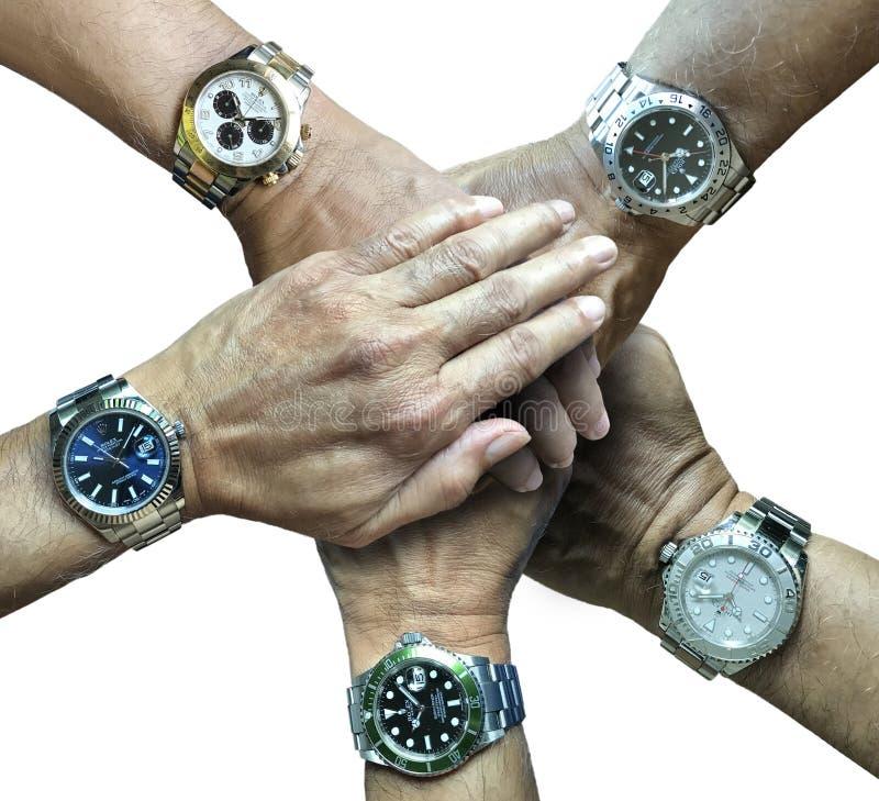 Vijf horloges van rolexsporten in vijf handen stock foto's