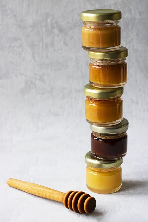 Vijf isoleren de Kleine glaskruik met metaal GLB met verschillende soorten en de kleuren van honing op een ander en lepel en  stock afbeelding