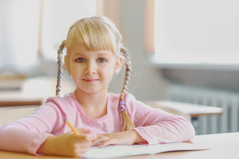Vijf jaar de oude van het blondemeisje zittings bij klaslokaal en het schrijven royalty-vrije stock fotografie